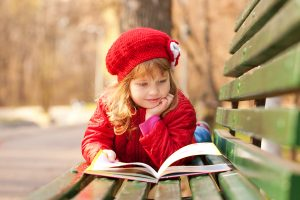 Happy smiling little girl reading interesting book in the park.