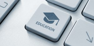 Button with graduation cap icon on a modern computer keyboard. Online education concept.